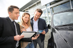 Car dealer showing vehicles on sale. Car dealer showing vehicles to couple Stock Image