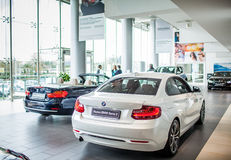 Car Dealer Showroom. ROME, ITALY - MARCH 10, 2014: Agents selling BMW cars inside car dealer showroom. The BMW Group recorded increasing of sales in Italy Royalty Free Stock Photography