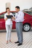 Car dealer woman. Car dealer explaining sales contract to young women buying a car Stock Image