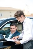 Car dealer and young man signing a contract Stock Images
