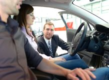 Car dealership advice - sellers and customers when buying a car royalty free stock photo