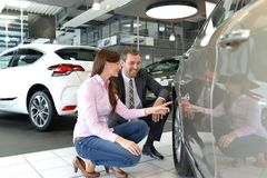 Car dealership advice - sellers and customers when buying a car. Techtalk about the tires royalty free stock photo