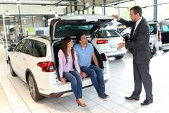 Car dealership advice - sellers and customers when buying a car royalty free stock image