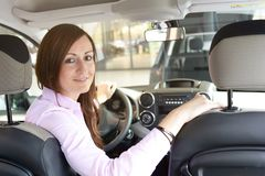 Car dealership advice - sellers and customers when buying a car. Smiling woman sitting in the car stock photography