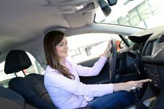 Car dealership advice - young woman sitting and testing in a new royalty free stock images