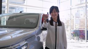 Car dealership, portrait of happy auto shop worker Asian woman pats vehicle with delight and shows keys to new machine. For sale in showroom close-up stock footage