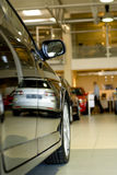 Car dealership showroom. Reflection of silver car off black car at car dealership showroom royalty free stock photography
