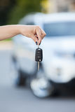 Car defocused on background and woman hand with key Stock Photography