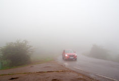 The car in dense fog. The red car goes on the twisting road in dense fog with the lit headlights Stock Photo