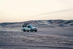 Car in desert, Hurghada, Egypt. Hurghada, Egypt - February 26, 2017: car in desert. 4x4 jeep toyota land cruiser driving in sand dunes on white sky background royalty free stock photos