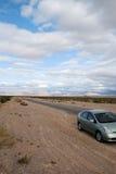 Car on desert road Stock Photos