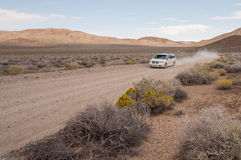 Car on desert road. Car on unpaved desert road swirling up dust behind it in Death Valley National Park, USA Royalty Free Stock Photo