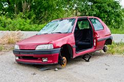 Car destroyed and dismembered to sell the pieces. Red car destroyed with glass destroyed and without wheels that were stolen and sold Royalty Free Stock Images
