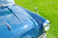 Car detail. Close up of a retro blue car against grass background stock images