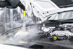 Car detailing. Car washing cleaning engine. Cleaning car engine using hot steam. Hot steam engine washing. Soft lighting. Car wash. Station worker cleaning royalty free stock photography
