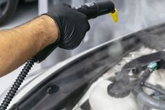Car detailing. Car washing cleaning engine. Cleaning car engine using hot steam. Hot steam engine washing. Soft lighting. Car wash. Station worker cleaning stock image
