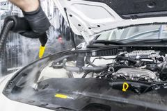 Car detailing. Car washing cleaning engine. Cleaning car engine using hot steam. Hot steam engine washing. Soft lighting. Car wash. Station worker cleaning royalty free stock photos