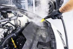 Car detailing. Car washing cleaning engine. Cleaning car using hot steam. Hot Steam engine washing. Soft lighting. Car washman wor. Ker cleaning vehicle stock image