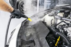 Car detailing. Car washing cleaning engine. Cleaning car using steam. Steam engine washing. Soft lighting. Car washman worker clea. Ning automobile royalty free stock images