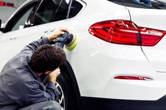Car detailing - Hands with orbital polisher in auto repair shop.  royalty free stock photography