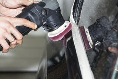 Car detailing - Hands with orbital polisher in auto repair shop. Selective focus. Car detailing - Hands with orbital polisher in auto repair shop. Selective royalty free stock image