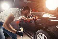 Car detailing - the man holds the microfiber in hand and polishes the car Stock Photo