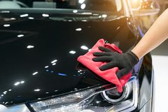 Car detailing - the man holds the microfiber in hand and polishes the car. Selective focus.  royalty free stock photography