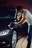 Car detailing - man with orbital polisher in auto repair shop. Selective focus. Car detailing - Hands with orbital polisher in auto repair shop. Selective focus stock photo