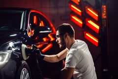 Free Car Detailing - Man With Orbital Polisher In Auto Repair Shop. Selective Focus. Stock Photo - 105652940