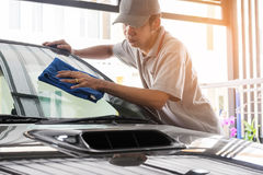 Car detailing and valet concepts. Auto service staff in grey uniform wipe the car glass with microfiber cloth-car detailing and valet concepts Stock Image