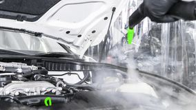Car detailing. Washing and cleaning engine. Cleaning car engine using hot steam. Hot steam engine washing. Car wash station. Man c stock photos