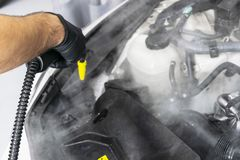 Car detailing. Car washing cleaning engine. Cleaning car engine using hot steam. Hot steam engine washing. Soft lighting. Car wash. Station worker cleaning stock photography