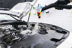 Car detailing. Car washing cleaning engine. Cleaning car using steam. Steam engine washing. Soft lighting. Car washman worker clea. Ning automobile stock images