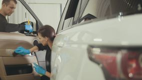 Car detailing - woman is cleaning dashboard in luxury vehicle Royalty Free Stock Images