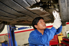 Car diagnostic. Concentrated Asian mechanic examining car in garage royalty free stock photo