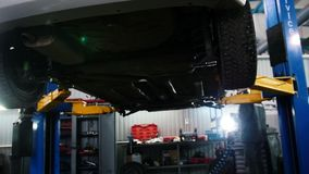 Car diagnostic - mechanic unscrewing device while working under a lifted automobile, slider shot. Backlight stock video footage