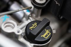 Car dipstick for oil level measurements. Checking the parameters. Of the car engine. Place - workshop Stock Photos