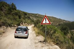Car on dirt road with caution sign. Stock Photos