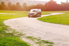 Car on dirt road curve and green grass park Royalty Free Stock Images