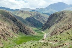 Car on dirt road in deep canyon of Tien Shan Royalty Free Stock Photo