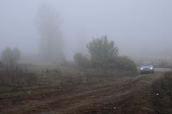 Car on the Dirt Road on the Foggy Day Stock Photos