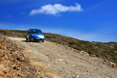 The car on a dirt road on a mountain slope. Greece Stock Photos