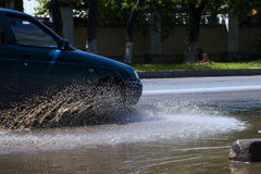 Car in dirty puddle on street Stock Photos