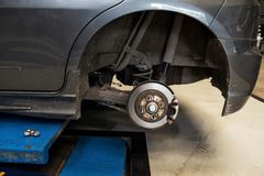 Car Disc Brake to repair in garage. Disc Brake of vehicle to be repaired. Automobile mechanic in process of new tire replacement. Car fix in garage Stock Images