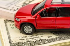 Car on dollar bills. A car stands on dollar banknotes. cost of buying a car, fuel, insurance and other car costs stock photography