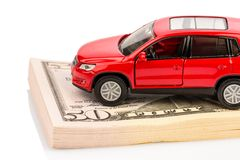 Car on dollar bills. A car stands on dollar banknotes. costs for the purchase of automobiles, gasoline, insurance and other car costs royalty free stock photos