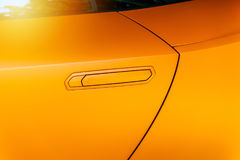 Car door handle of an orange modern car Royalty Free Stock Photo