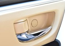 Car-door open handle. Silver car-door open handle on cream leather background as an auto part of motor vehicle Royalty Free Stock Photos
