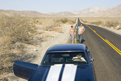 Car with door open for young couple hitchhiking on desert road, elevated view Royalty Free Stock Photo
