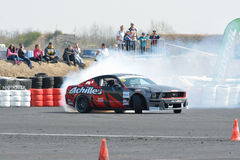 Car drifting on a race track. Muscle car drifting on a race track with lots of smoke from wheels. Drift show at the airport, Tököl, Hungary. Photo taken to Stock Image